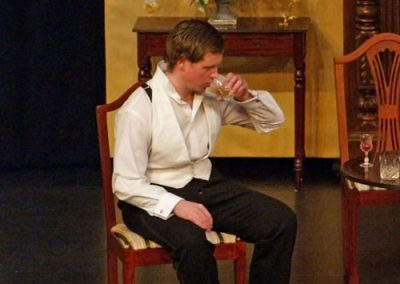 Eric Birling takes to drink as the family's situation worsens