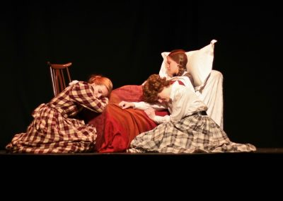 Jo (Ellie Pickering) and Meg (Jessica Hocking) gather round sick Beth (Tabitha Havenhill)